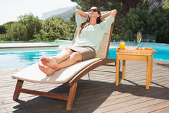 Woman relaxing by pool with breakfast on table Royalty Free Stock Photo