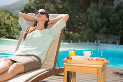 Woman relaxing by pool with breakfast on table Stock Photos