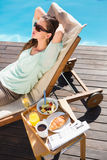 Woman relaxing by pool with breakfast on table Royalty Free Stock Photography