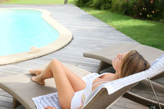 Woman relaxing by the pool Stock Images