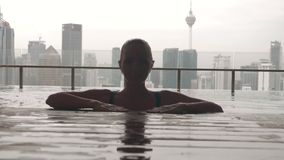 Woman relaxing in pool. Rear swimming pool with city view in slow motion.Happy girl enjoying vacation. Success, happiness concept stock video footage