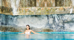 Woman relaxing in a pool at summer Stock Images
