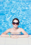 Woman relaxing by the pool in the summer in a bikini Royalty Free Stock Photography