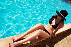 Woman relaxing by the pool Royalty Free Stock Photos