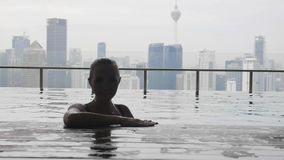 Woman relaxing in pool. Young beautiful woman jumping out of water in roof top swimming pool with city view in slow motion.Happy girl enjoying vacation.Success stock video footage