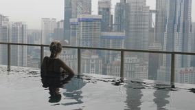 Woman Relaxing in Pool. Young beautiful woman and her reflection in roof top swimming pool with city view in slow motion.Happy girl enjoying vacation.Success stock footage