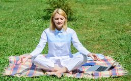 Woman relaxing practicing meditation. Every day meditation. Reasons you should meditate every day. Clear your mind. Girl. Meditate on rug green grass meadow stock images