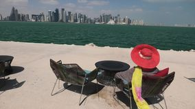 Woman relaxing in Qatar. Elegant woman with red sunhat in the wind by Doha Bay. Lifestyle caucasian tourist enjoys skyscrapers of Doha Downtown skyline at famous stock video