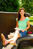 Woman relaxing reading a book. A woman 40ish relaxes and reads a book in the park royalty free stock photo