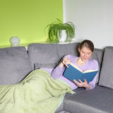 Woman relaxing reading on a sofa Royalty Free Stock Images
