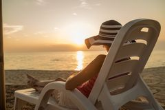 Woman relaxing on a recliner at the beach. Woman in a large floppy sunhat relaxing on a recliner at the beach at sunset facing out over a tranquil ocean on her Royalty Free Stock Photos