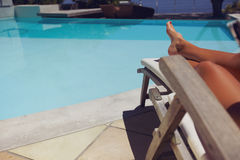 Woman relaxing on a recliner by poolside. Young woman relaxing on a recliner by swimming pool. Legs of female sitting on chair taking sunbath Stock Images