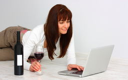 Woman with wine and laptop (computer) Royalty Free Stock Images