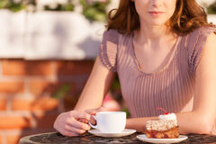Woman relaxing at the restaurant. Cropped image of attractive young woman drinking coffee at the outdoor cafe Stock Image