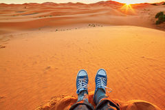 Woman relaxing on sand dunes and looking at sunrise in Sahara Desert Royalty Free Stock Photography