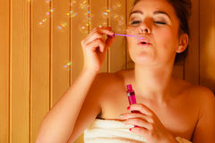 Woman relaxing in sauna room blowing soap bubbles Royalty Free Stock Photo