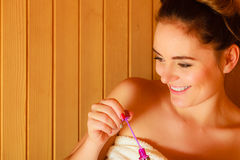 Woman relaxing in sauna room blowing soap bubbles Stock Photography