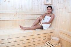 Woman relaxing in sauna room. Stock Image