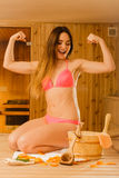 Woman relaxing in sauna showing off muscles. Royalty Free Stock Photography