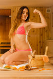 Woman relaxing in sauna showing off muscles. Royalty Free Stock Images