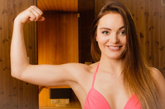 Woman relaxing in sauna showing off muscles. Royalty Free Stock Photos