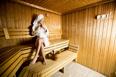 Woman relaxing in the sauna at spa center. Young woman relaxing in the sauna at spa center Stock Images