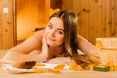 Woman relaxing in sauna. Spa wellbeing. Woman with bucket ladle and petals relaxing in finnish sauna. Attractive girl in bikini resting. Spa wellbeing pleasure Stock Photo
