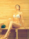 Woman relaxing in sauna. Stock Photos