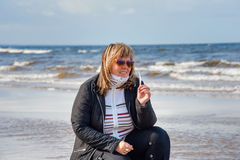 Woman relaxing at the sea. Mature chubby woman relaxing at the Baltic sea in autumn day royalty free stock images