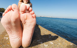 Woman relaxing by seaside showing her dry feet sole Royalty Free Stock Photography