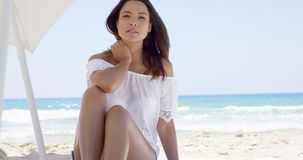 Woman relaxing in the shade of a beach umbrella stock video