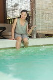 Woman relaxing on side of private swimming pool Stock Photography