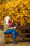 Woman relaxing sitting on bench in park using tablet Royalty Free Stock Images