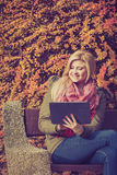 Woman relaxing sitting on bench in park using tablet Royalty Free Stock Photography