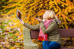 Woman relaxing sitting on bench in park using tablet Stock Photo