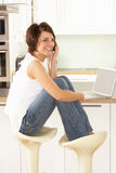 Woman Relaxing Sitting In Kitchen Talking On Phone Stock Photography