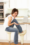 Woman Relaxing Sitting In Kitchen Talking On Phone Royalty Free Stock Photography