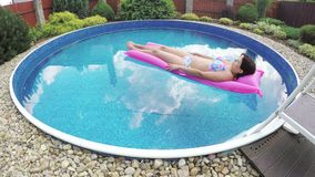 Woman relaxing in a small home pool stock footage