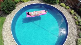 Woman relaxing in a small home pool stock video footage