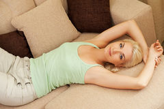 Woman relaxing on a sofa Stock Images