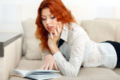 Woman relaxing on sofa with book Stock Photography