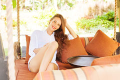 Woman relaxing at an sofa. Happy brunette woman relaxing at an outdoor sofa Stock Images