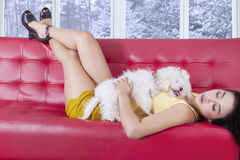 Woman relaxing on the sofa with her dog Stock Photo