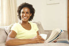 Woman Relaxing On Sofa At Home Stock Photo