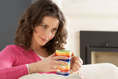 Woman Relaxing On Sofa At Home Drinking Coffee Royalty Free Stock Image
