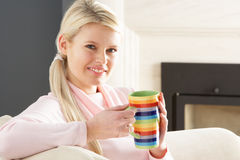 Woman Relaxing On Sofa At Home Drinking Coffee Royalty Free Stock Images