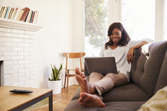 Woman Relaxing On Sofa At Home Using Laptop royalty free stock images