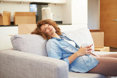 Woman Relaxing On Sofa With Hot Drink In New Home. Happy Woman Relaxing On Sofa With Hot Drink In New Home Looking Above Royalty Free Stock Photography