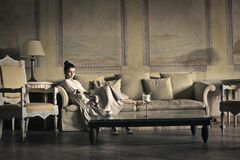 Woman relaxing on the sofa. Lady lying on a sofa Stock Photography