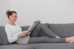 Woman relaxing on a sofa with a newspaper Stock Photos